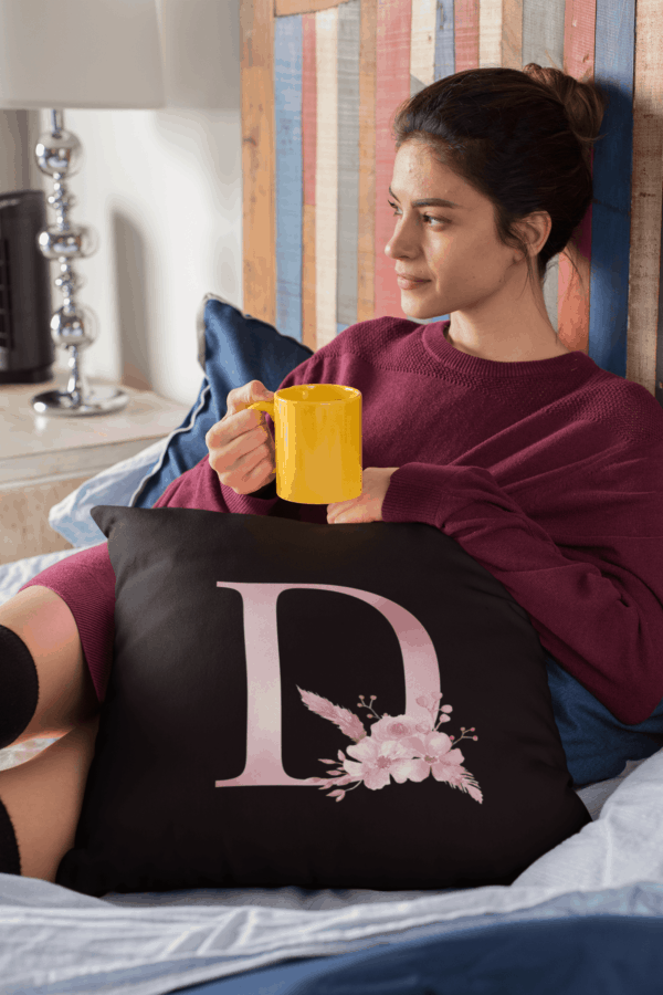 Custom Printed Monogram Letter D on Black Pillow Case pillow mockup of a woman sitting cozily on her bed drinking tea