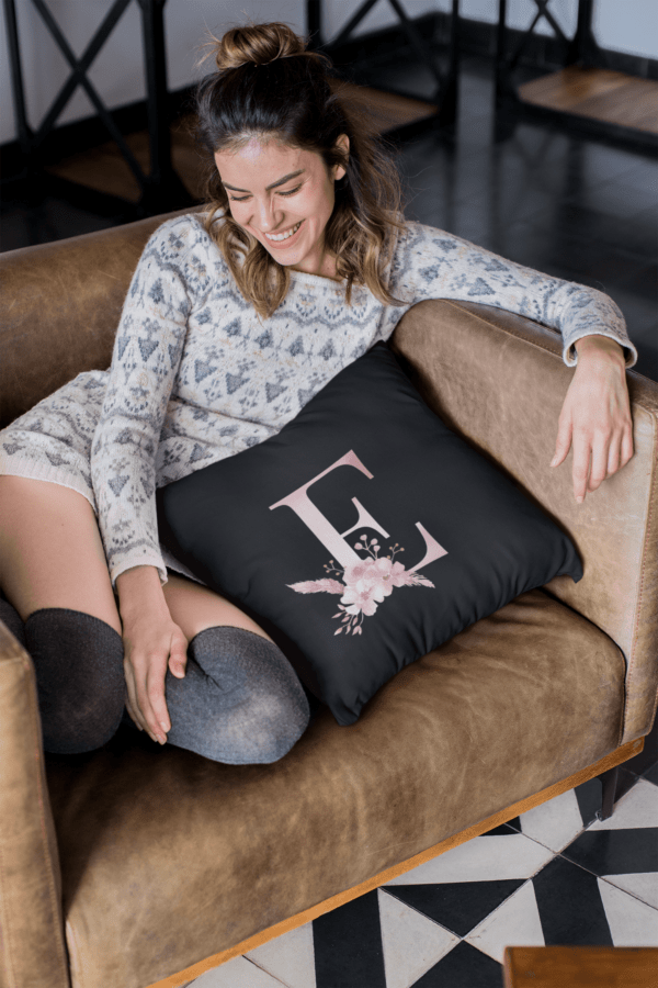 Custom Printed Monogram Letter E on Black Pillow Case pillow mockup of a smiling girl sitting on a sofa