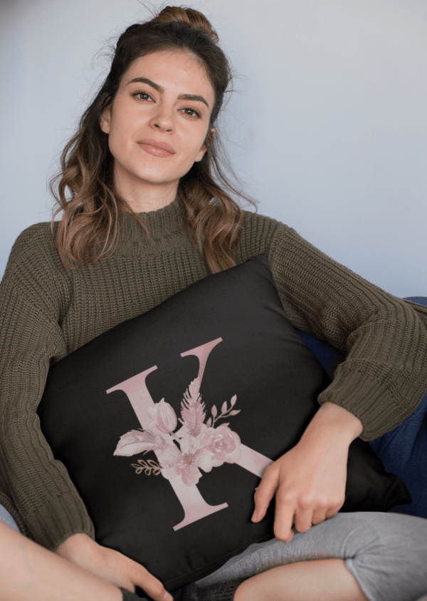 Custom Printed Monogram Letter K on Black Pillow Case mockup of a woman holding a square pillow while sitting
