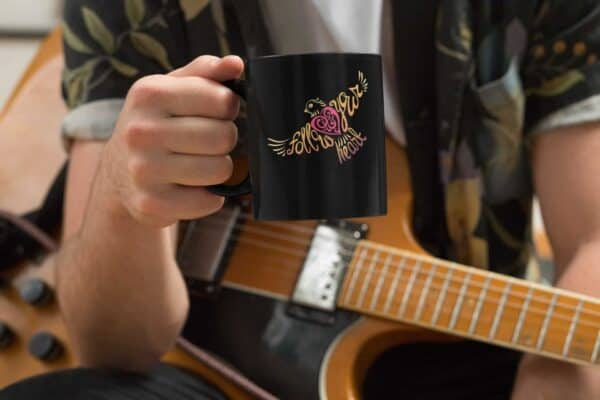 Follow Your Heart Coffee Mug Design Black mockup of a musician holding an 11oz coffee mug