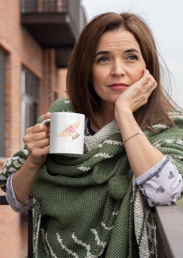 Follow Your Heart Coffee Mug Design White mockup of a middle aged woman holding an 11oz coffee mug outside