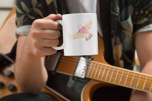 Follow Your Heart Coffee Mug Design White mockup of a musician holding an 11oz coffee mug