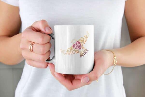 Follow Your Heart Coffee Mug Design White mockup of a woman holding an 11 oz coffee mug