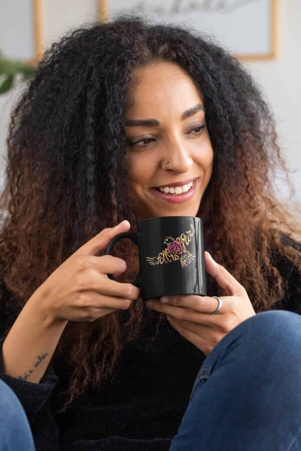 Follow Your Heart Coffee Mug Design mockup of a curly haired woman with an 11oz black mug in her hands