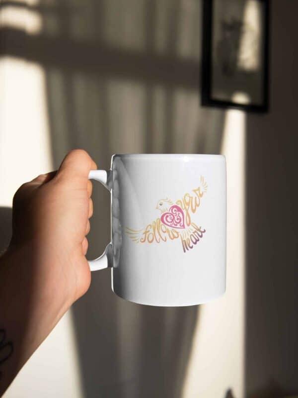 Follow Your Heart Coffee Mug Design on White sticker mockup featuring a man holding a coffee mug