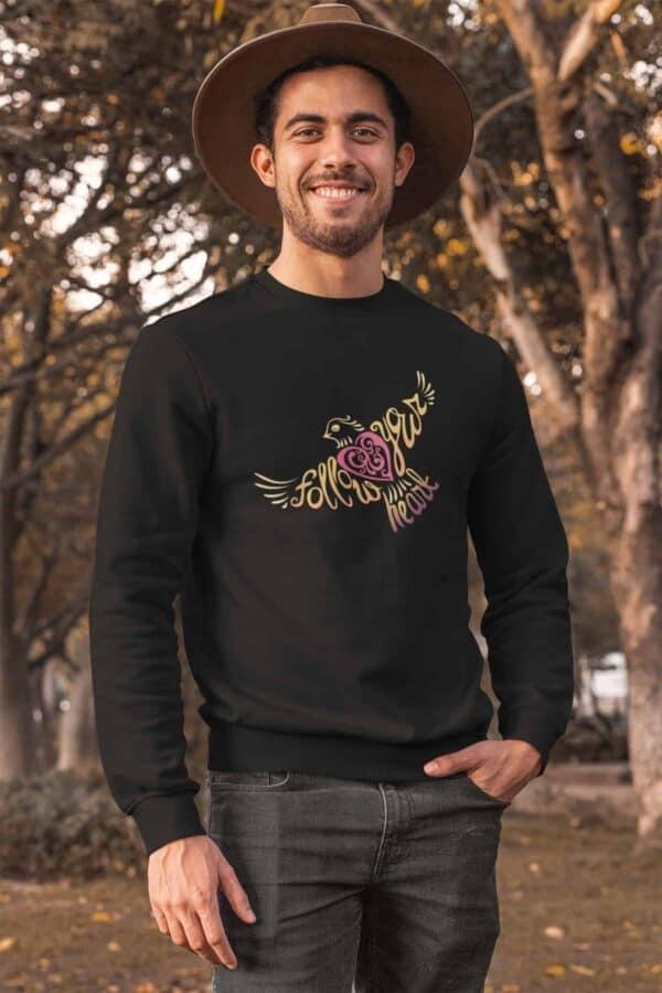 Follow Your Heart Crewneck Sweat Shirt Design Black crewneck sweatshirt mockup of a man posing at a park during autumn
