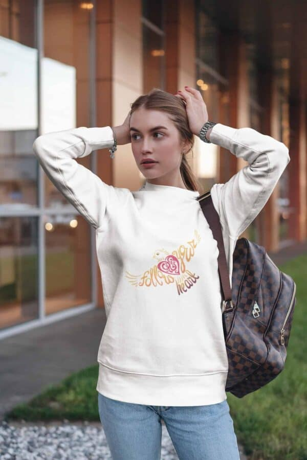 Follow Your Heart Crewneck Sweat Shirt Design White sweatshirt mockup of a woman with her hands on her head