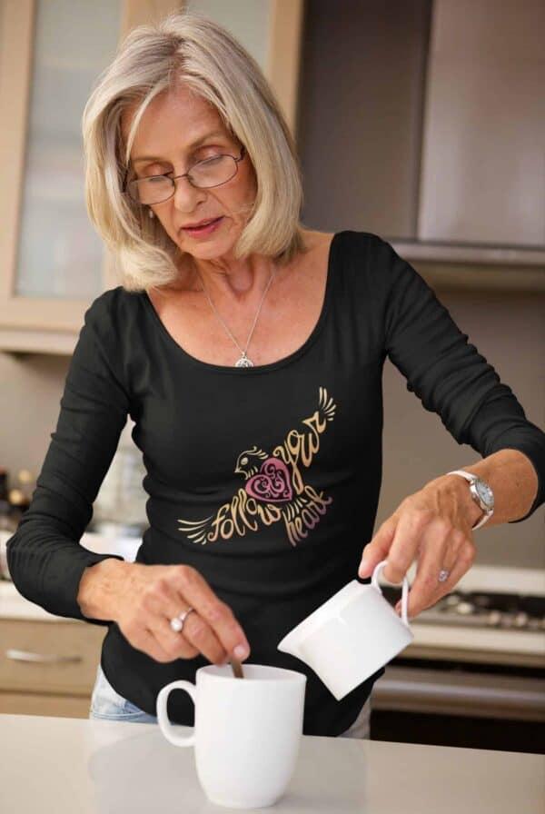 Follow Your Heart Long Sleeve T-Shirt Inspirational Design mockup of a senior woman making coffee