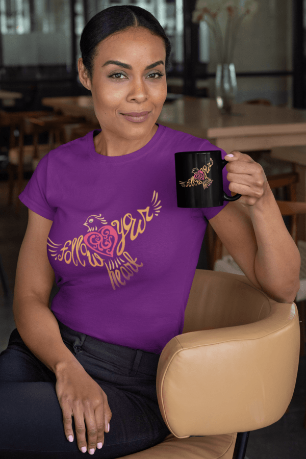 Follow Your Heart T-Shirt Design mockup of a woman sitting on a chair holding an 11oz coffee mug